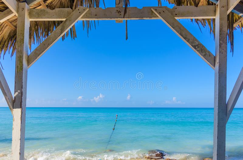 Hot tropical day the Caribbean sea pier with pergola. Palm leaves stock photo