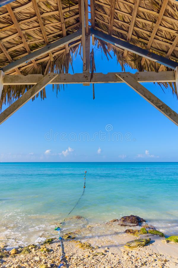 Hot tropical day the Caribbean sea pier with pergola. Palm leaves royalty free stock photos