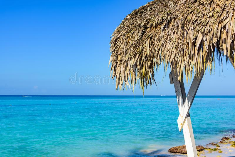 Hot tropical day the Caribbean sea pier with pergola. Palm leaves royalty free stock image