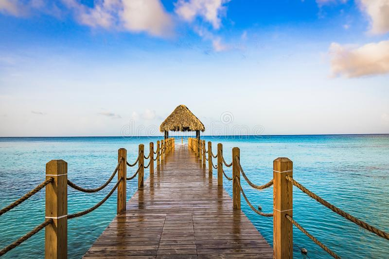 Hot tropical day the Caribbean sea pier with pergola. Palm leaves royalty free stock photography