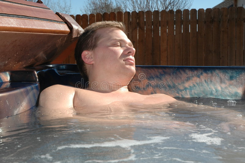 Hot Tub. Man relaxs in his hot tub after long week of work. Sitting in a hot tub with eyes closed stock photo