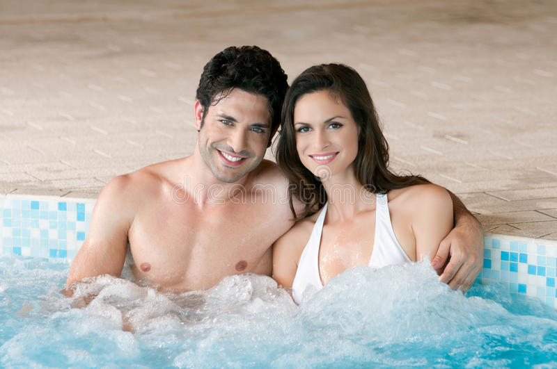 Hot tub with love. Smiling loving couple relaxing together on a jacuzzi pool at spa