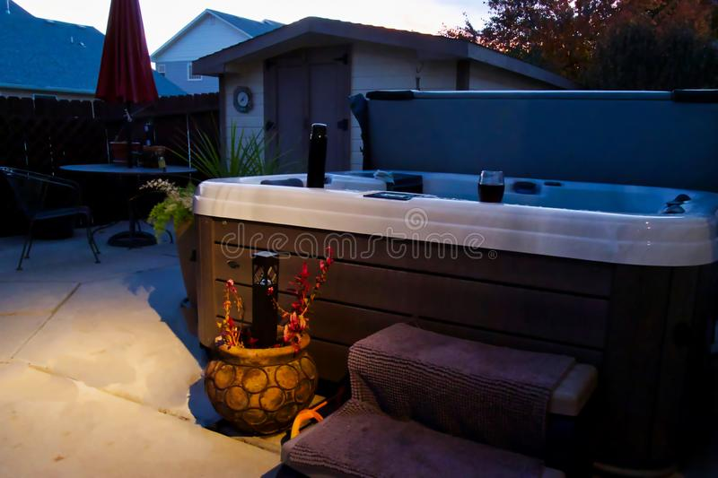 Hot Tub Summer Night. Hot tub, water bottle, and a glass of wine on a relaxing summer evening royalty free stock images