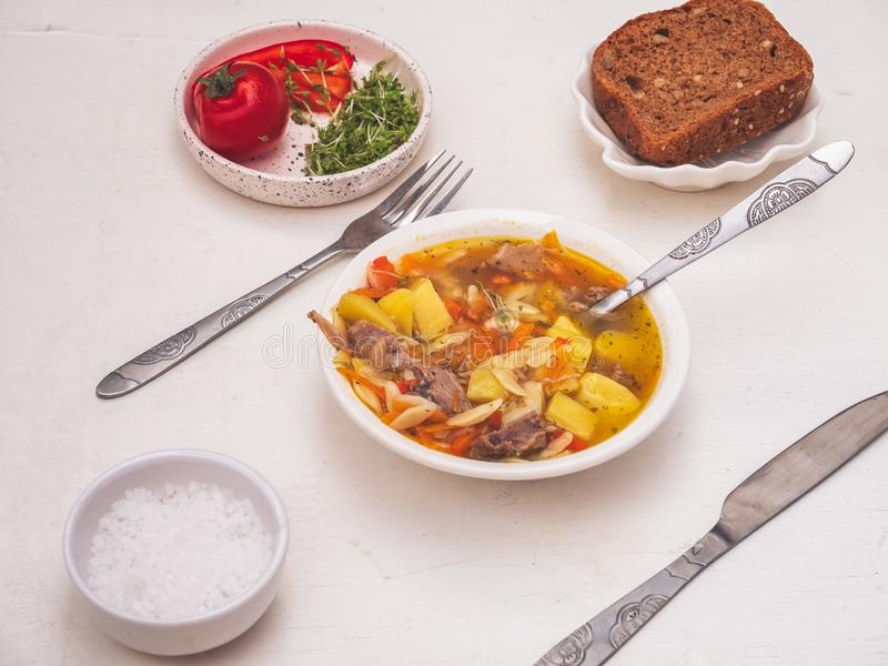Hot turkey soup with spices and pasta in a deep plate on a white table, cutlery laid out next. stock images