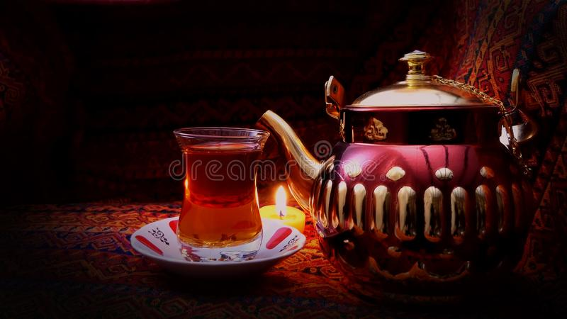 Hot Turkish glass of red tea with artistic teapot. Old Arabic Teapot with smoke over dark background. Arabian Nights background. Hot Turkish glass of red tea royalty free stock images