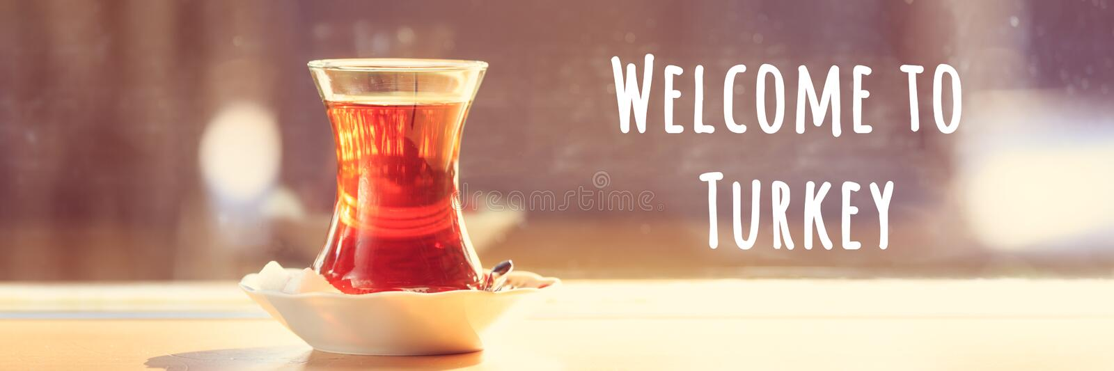 Hot turkish tea outdoors near glass wall. Turkish tea and traditional turkish culture concept. Welcome to Turkey text. Hot turkish tea outdoors near glass wall royalty free stock images