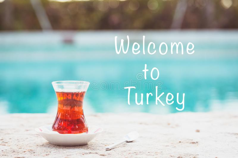 Hot turkish tea outdoors near water. Turkish tea and traditional turkish culture concept. Welcome to Turkey text. Hot turkish tea outdoors near water. Turkish stock photography