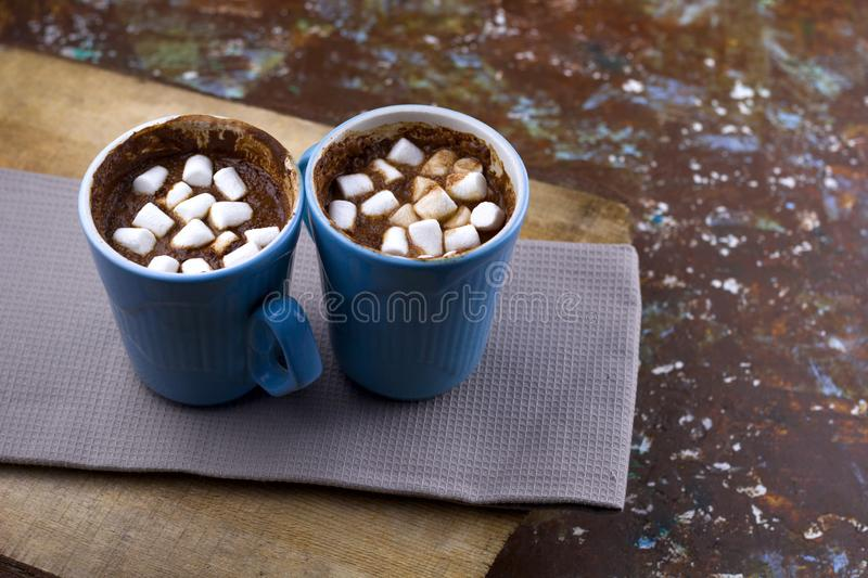 Hot warming chocolate with marshmallows. On wooden table served on cloth copy space royalty free stock photo