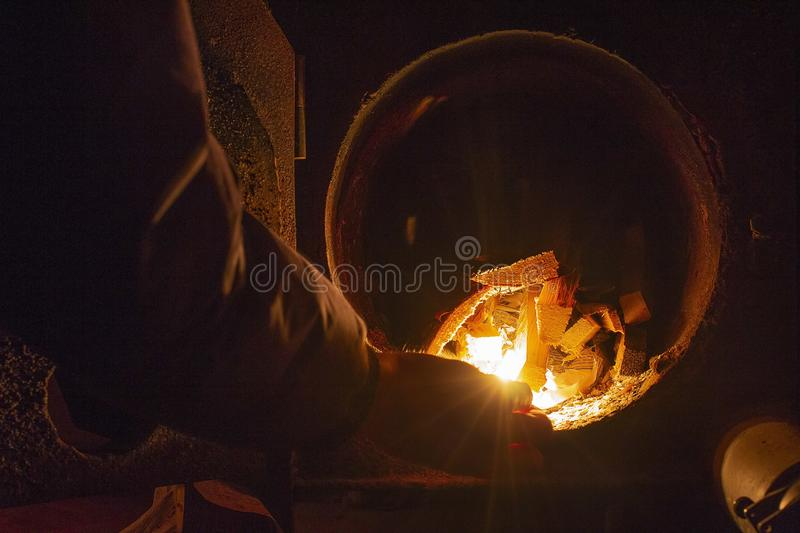 Hot water boiler with open door and fire inside and scoop with coal royalty free stock photography