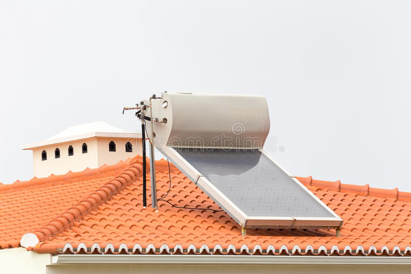 Hot water boiler with solar panel on roof. Of house stock photography