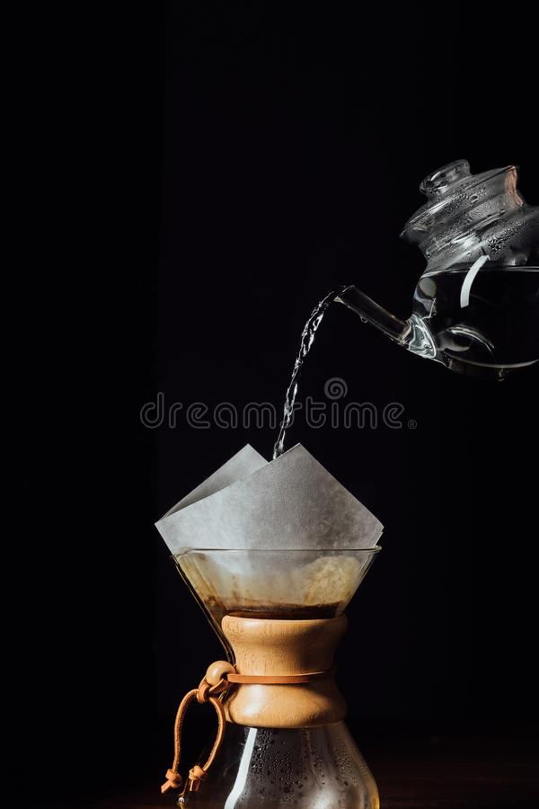 Hot water pouring into chemex with filter cone, isolated on black royalty free stock photo