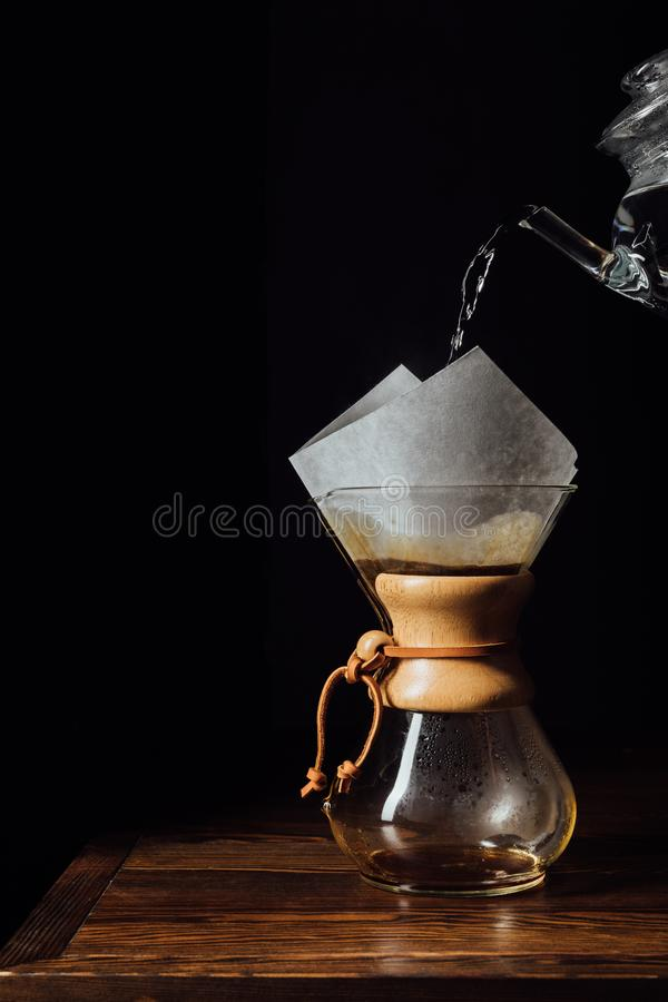 Hot water pouring into chemex with filter cone on wooden table stock image