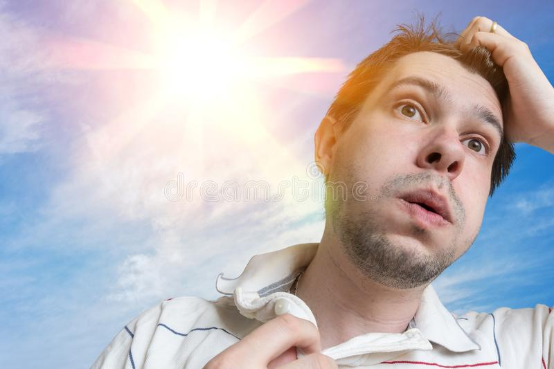 Hot weather concept. Young man is sweating. Sun in background.  royalty free stock image