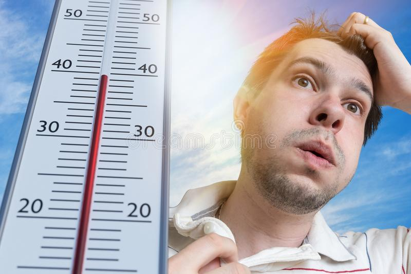 Hot weather concept. Young man is sweating. Thermometer is showing high temperature. Sun in background royalty free stock photos