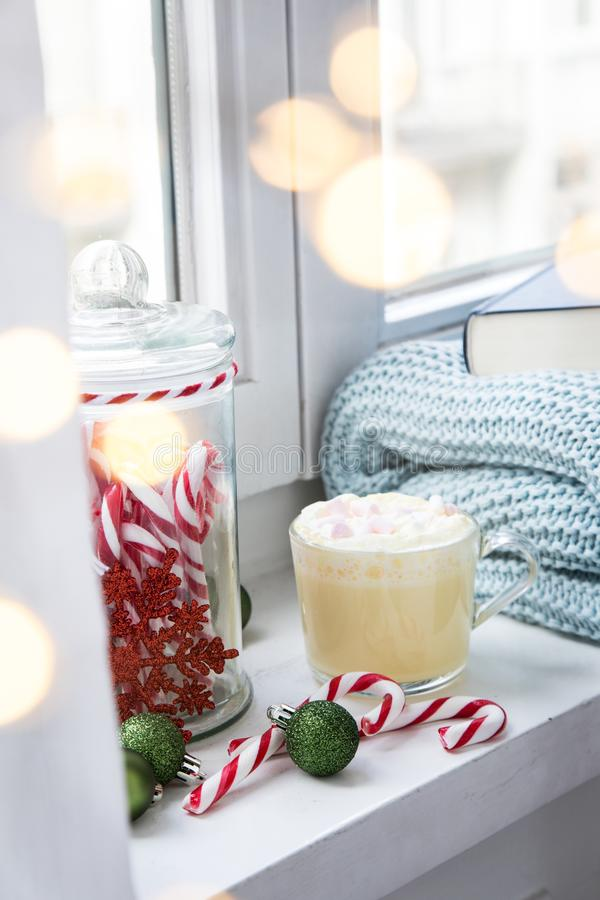 Hot white chocolate with whipped cream and marshmallows on windowsill with cosy wool rug blanket and book at Christmas X-Mas. Advent weekend with light bokeh stock images