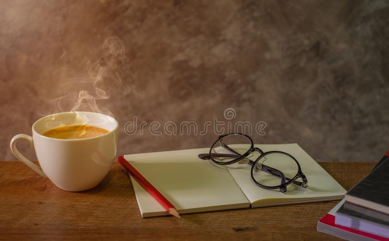 Hot white cup of fresh coffee, cappuccino on the wooden table with Blank open booklet, red pencil, glasses and stack of books to r royalty free stock image