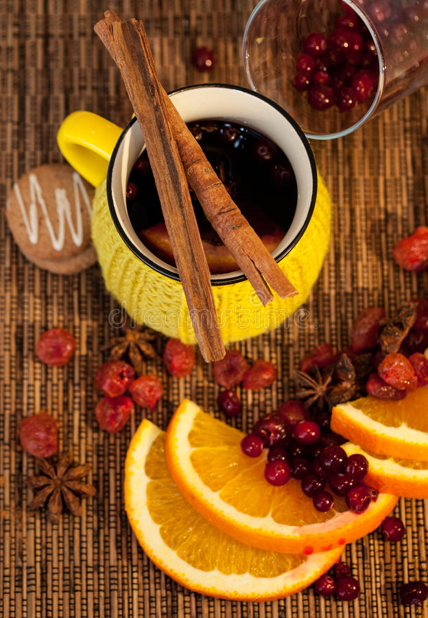 Hot wine cup and cinnamon sticks. Nice hot wine and cinnamon sticks and dried fruits composition royalty free stock images