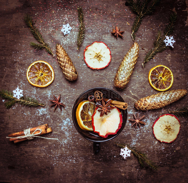Hot wine punch in dark cup with winter spices and fruits on wooden table royalty free stock photo