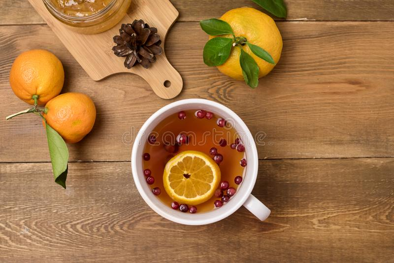 Hot Winter Berry Tea with Cranberries and Citrus Wooden Background Ripe Fruit Citrus Oranges Top View stock photo