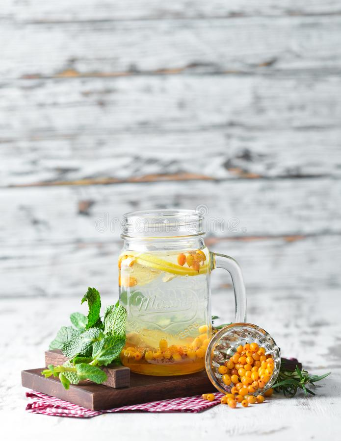 Hot winter tea from sea buckthorn. On a wooden background. Top view. Free copy space stock photo