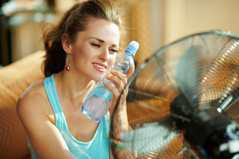 Hot woman with bottle of cold water using electric metallic fan. At modern home in sunny hot summer day stock images