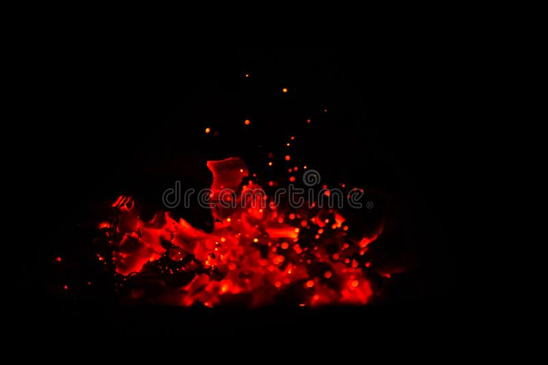 Hot wooden coals in the dark. Grill with hot coals and beautiful magic sparks with blue flame royalty free stock images