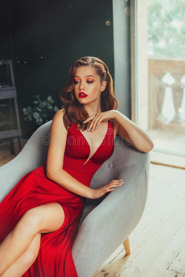 Hot young adult and imperious woman, dressed in a long scarlet red long dress, sexually shows her nude elegant leg royalty free stock photos