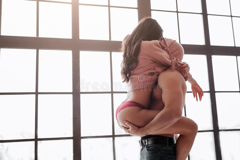 Hot young couple stand at window and hide heads under sweater. Woman sit on guy and embrace him with legs. Man hold her royalty free stock photos