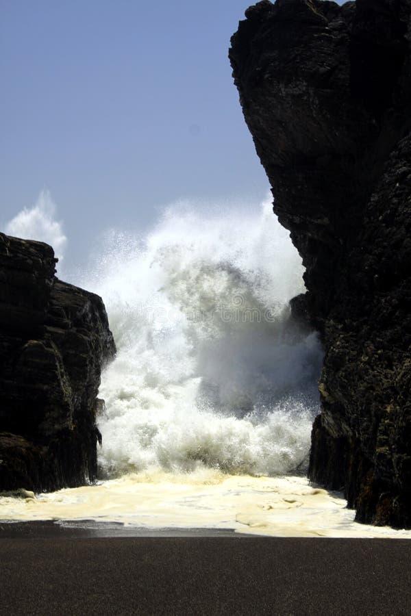 Hota den farliga väggen för det vita havet som trycker på vagga igenom, mellanrummet på den svarta lavasandstranden på Stilla hav arkivbilder