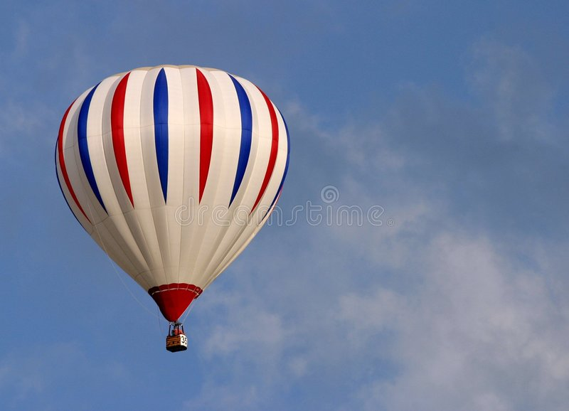 Hotair balloon. A Striped hotair balloon in flight stock photo