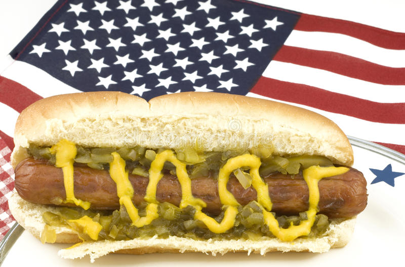 Hotdog with American Flag. A hotdog on a plate with an American flag background, selective focus on hotdog, horizontal with copy space royalty free stock photo