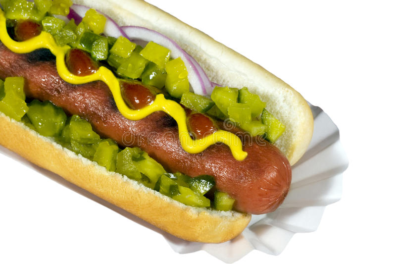 Hotdog on Bun. A grilled hotdog on bun topped with onion, mustard, ketchup and relish isolated on white background stock image