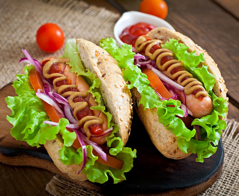 Hotdog with ketchup, mustard, lettuce and vegetables. On wooden table royalty free stock images
