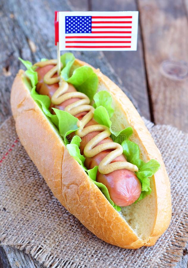 Hotdog sandwich with yellow mustard sauce and lettuce royalty free stock photo
