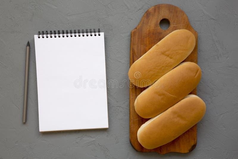 Hotdogbroodjes op een rustieke houten raad, lege blocnote met potlood op een grijze achtergrond, hoogste mening Ruimte voor tekst royalty-vrije stock afbeeldingen