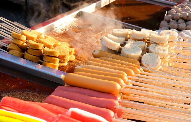 hotdogs e bolas de peixes em varas de madeira fotografia de stock royalty free