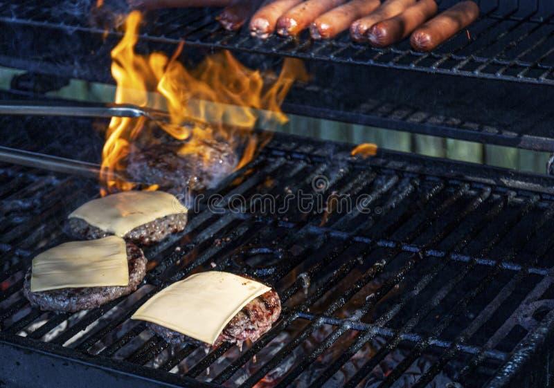 Hotdogs en cheeseburgers die met vlammen worden geroosterd die behandelen royalty-vrije stock foto's