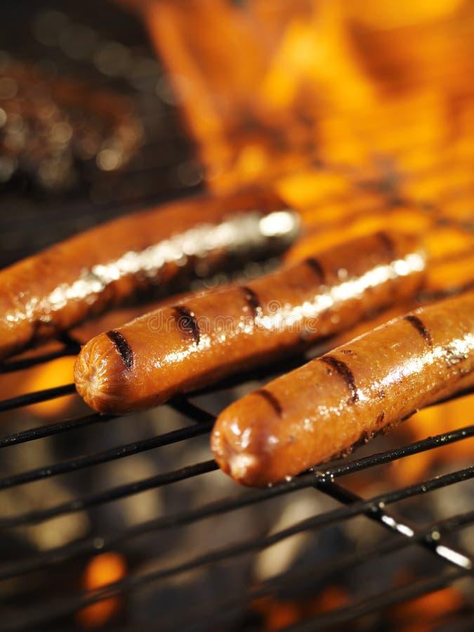 Hotdogs gotuje na płomiennym grillu zdjęcia stock