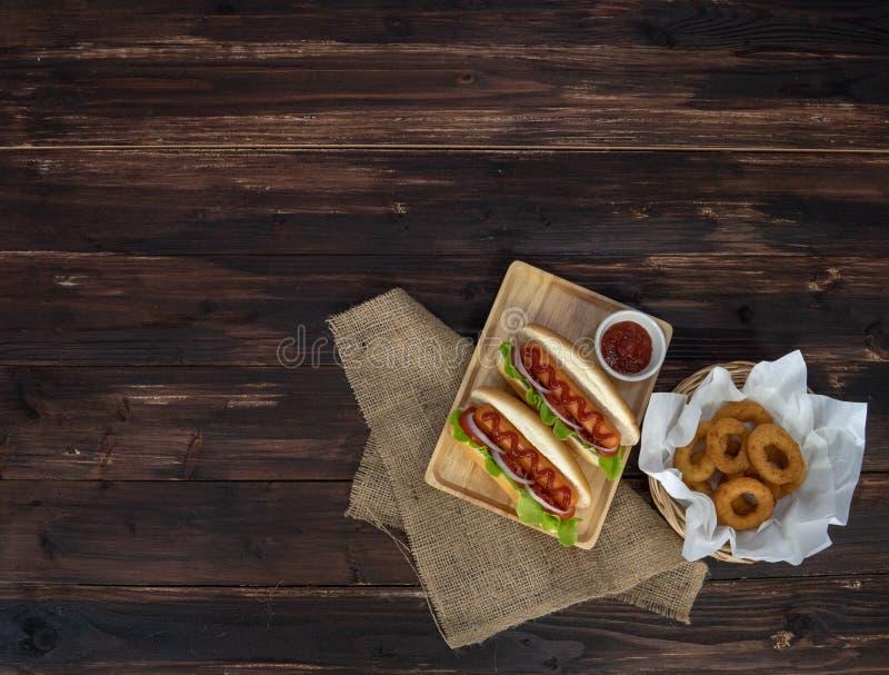 Hotdogs och stekte lökcirklar, beautifully ordnat som är aptitretande på den bruna trääta middag tabellen royaltyfri fotografi
