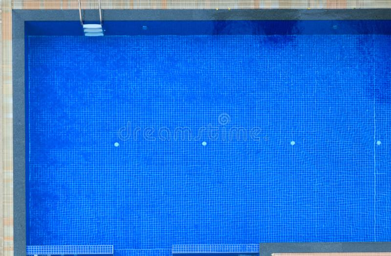 hotel's蓝色铺磁砖的游泳场背景顶视图  户外运动,休闲,锻炼,家庭活动,休闲 免版税库存照片