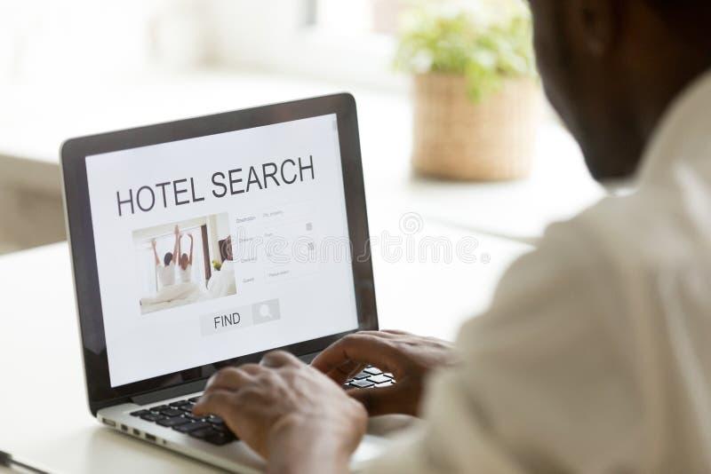 Hotel afroamericano de la ojeada del hombre en línea usando la búsqueda app en l fotografía de archivo libre de regalías