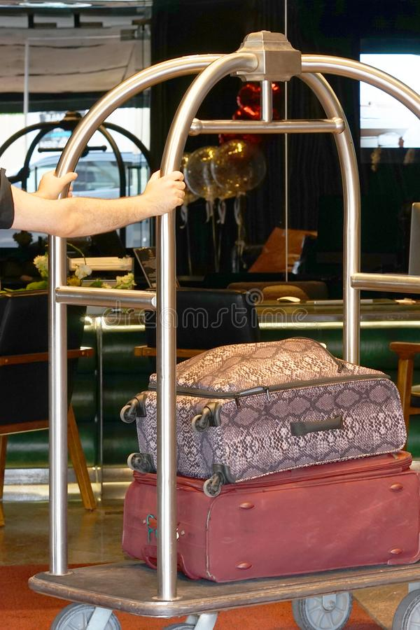 Hotel baggage cart. Close-up many suitcases on hotel luggage cart moving by bell boy. Baggage porter or bell boy bringing the suitcase of guests with a box van stock photo