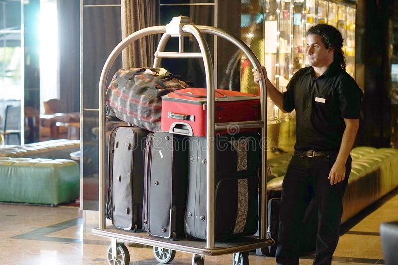 Hotel baggage cart. Closeup many suitcases on hotel luggage cart moving by bell boy. Baggage porter or bell boy bringing the suitcase of guests with a box van to stock image