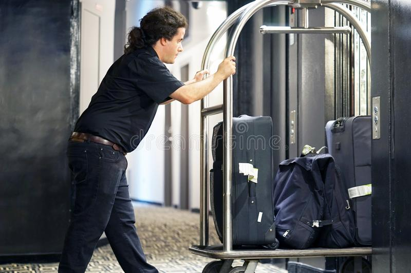 Hotel baggage cart. Closeup many suitcases on hotel luggage cart moving by bell boy. Baggage porter or bell boy bringing the suitcase of guests with a box van to royalty free stock photo