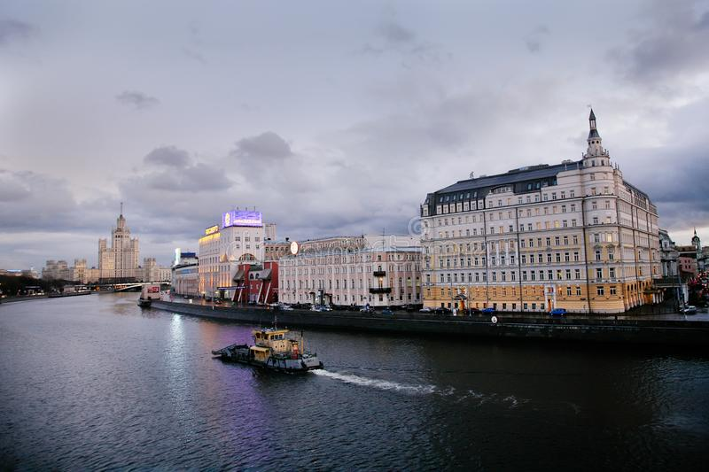 Moscow  river, Hotel Baltschug Kempinski. Hotel Baltschug Kempinski  and   building `Stalinskaya vysotka` -scyscraper of Stalin epoch  and  and tugboat sailing royalty free stock photography