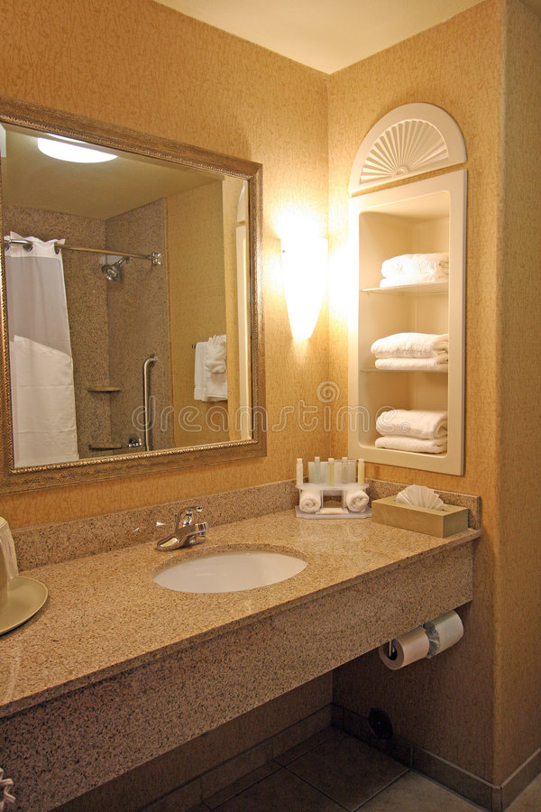 Hotel bathroom sink area. A hotel bathroom sink with mirror on wall, built-in shelves holding towels, small containers of shampoo and soaps, tissue, shower, and royalty free stock photo