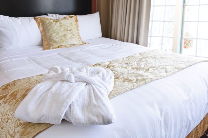 Hotel bed with bathrobe royalty free stock photos