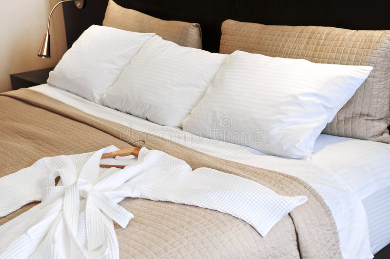 Hotel bed with bathrobe stock photography