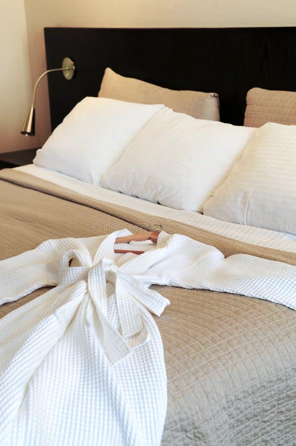Hotel bed with bathrobe royalty free stock photo