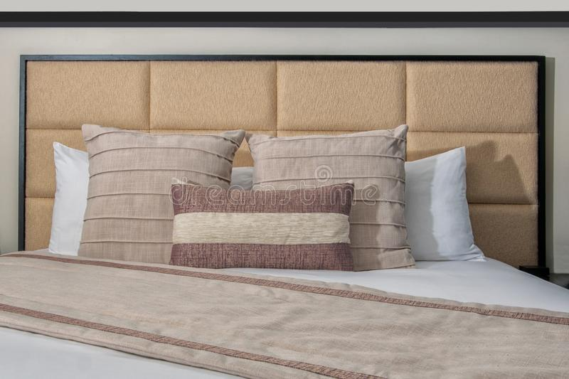 Hotel Bed, head board, pillows, comforter and white linen. Pure white linen bed sheets, pillows, headboard and comforter of hotel resort bed stock photos